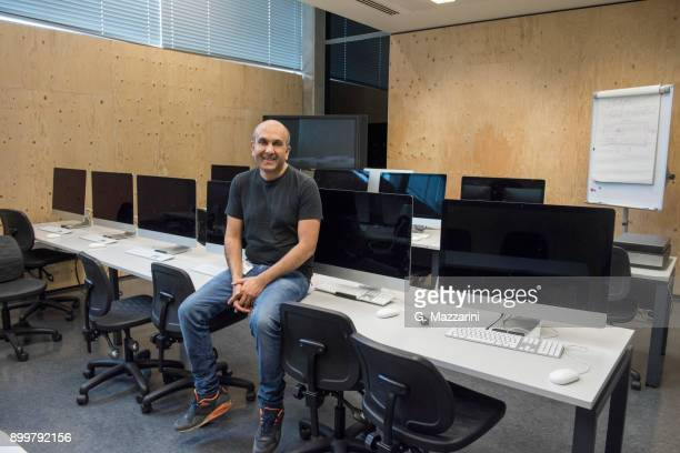 man sitting on desk in computer room looking at camera smiling - 校長 ストックフォトと画像