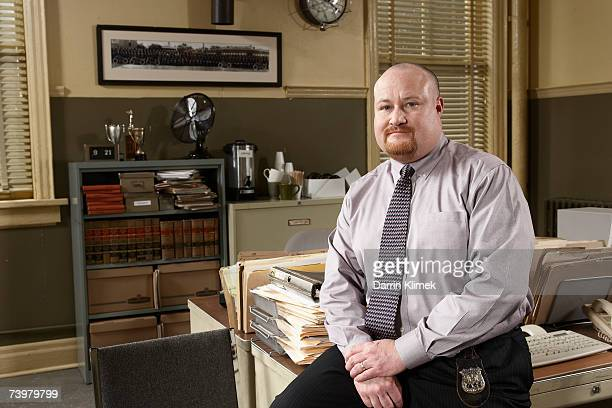 man sitting on desk in office, portrait - detective stock pictures, royalty-free photos & images