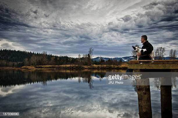 Man sitting on dock with his dog