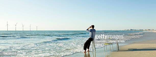 Man sitting on edge of desk at water's edge on beach looking at offshore wind turbines on horizon