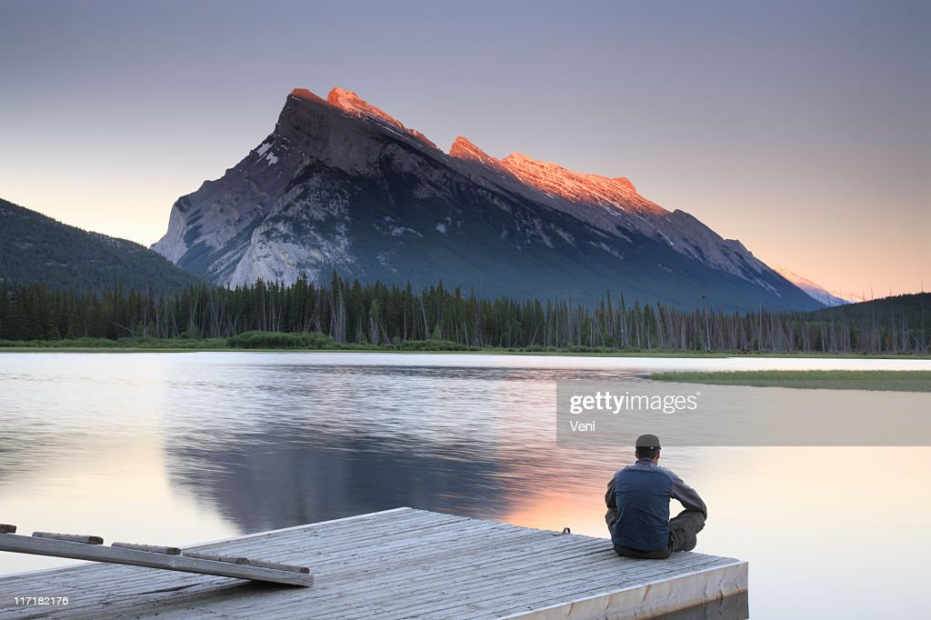 Man sitting on edge of dock by Mount Rundle, Banff : Stock Photo