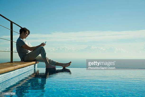 Man sitting on edge of infinity pool, text messaging with cell phone