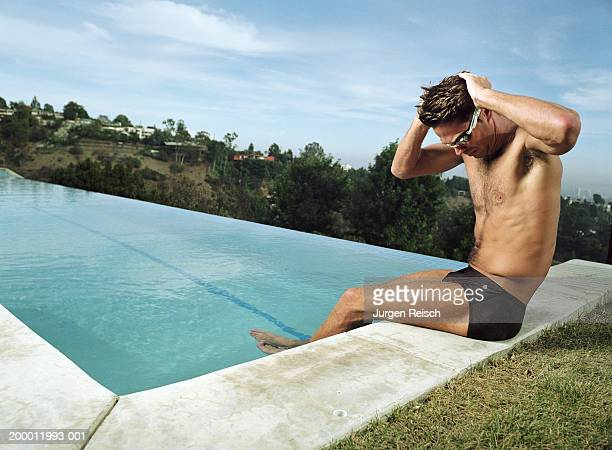 man sitting on edge of pool, putting on goggles - man wearing speedo stock photos and pictures