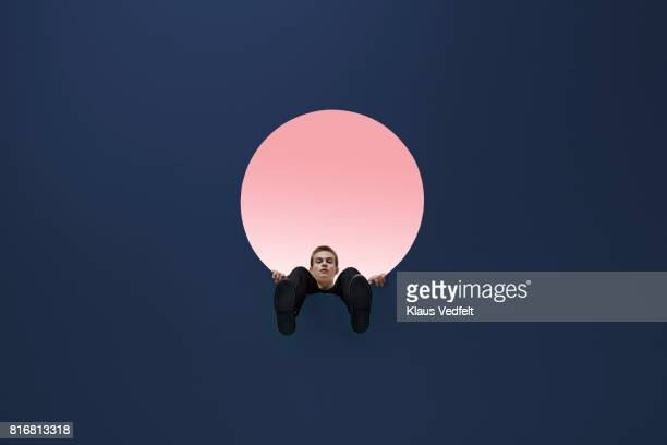 Man sitting on edge of round opening in coloured ceiling, looking down with feet dangling