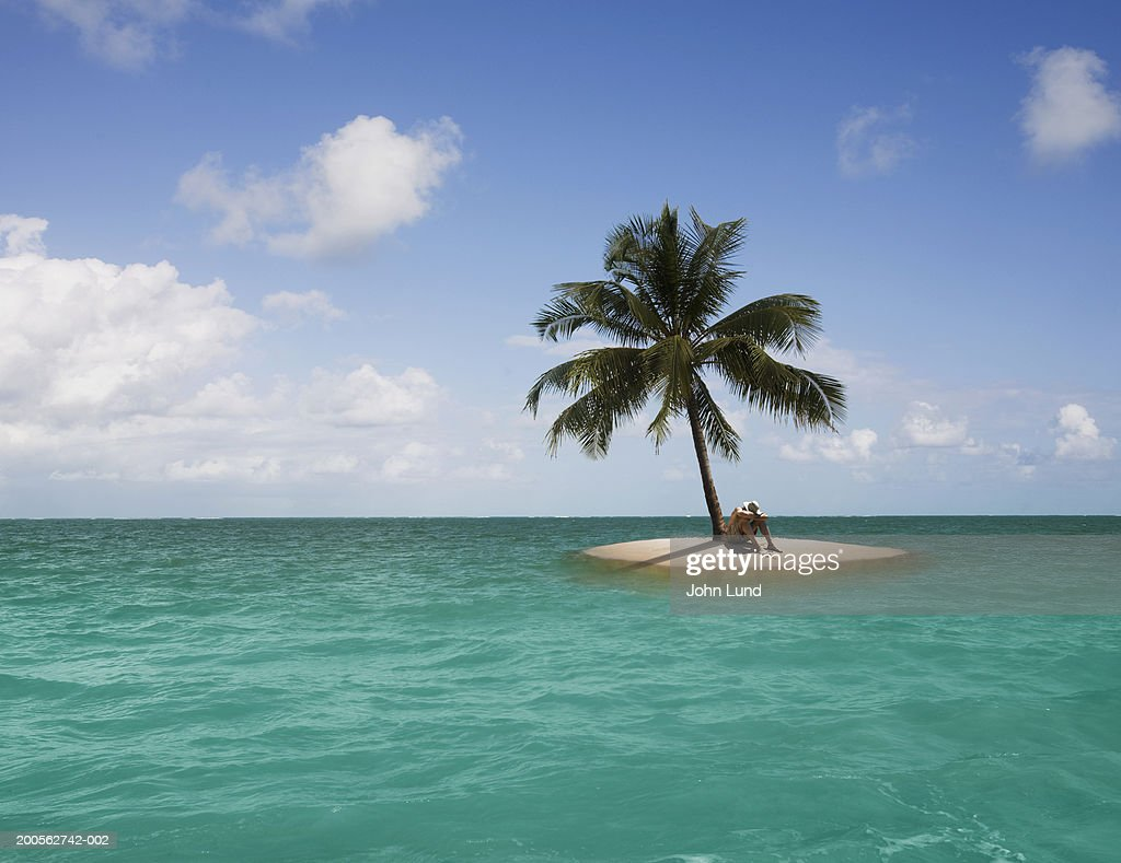 Man sitting on edge of small island with one palm tree : ストックフォト