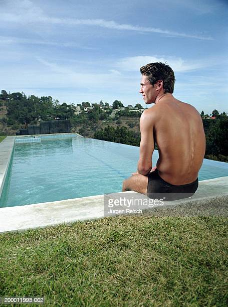 man sitting on edge of swimming pool - young men in speedos stock pictures, royalty-free photos & images