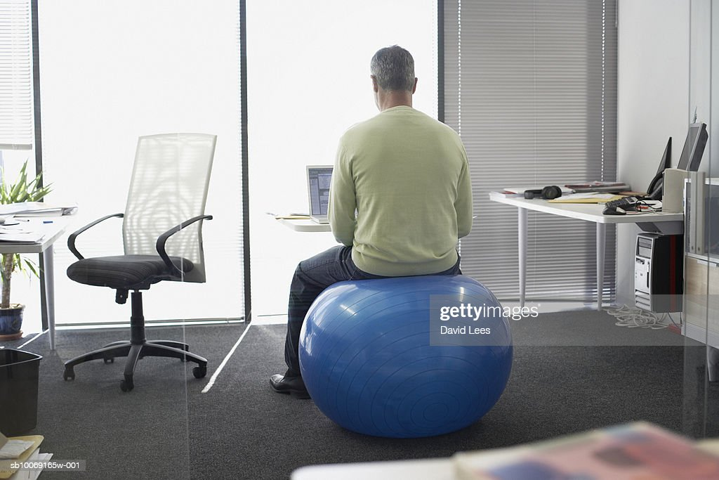 Man sitting on fitness ball working in office, rear view : Stockfoto