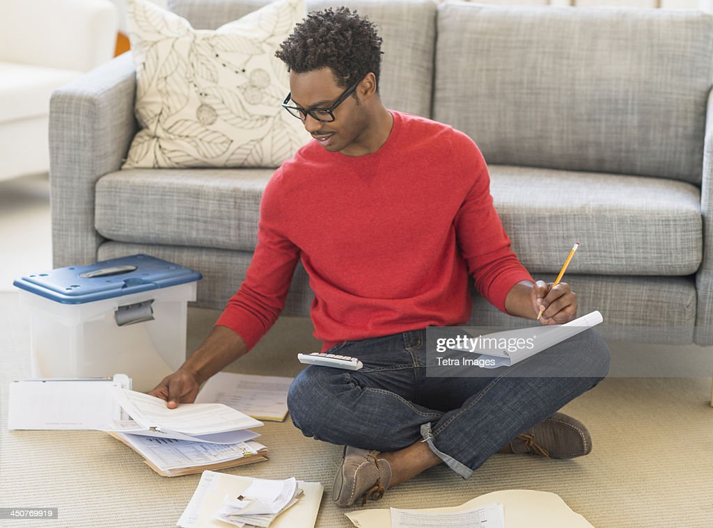 Man sitting on floor in living room and calculating bills : Stock Photo