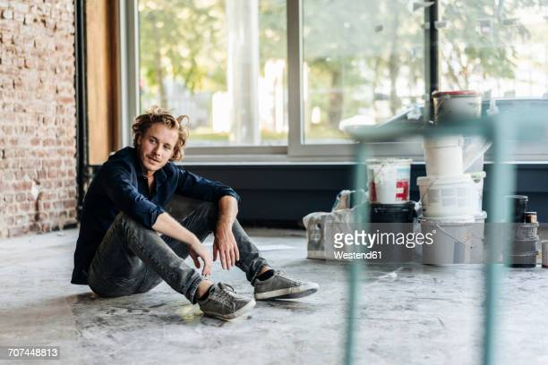 man sitting on floor in unfinished room - eröffnung stock-fotos und bilder