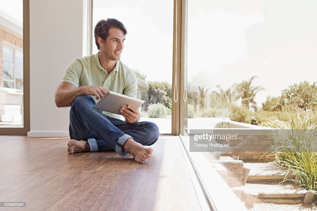 Man sitting on floor using tablet pc : Stock Photo