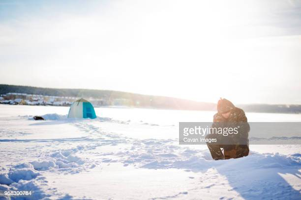 man sitting on frozen lake against sky on sunny day - extreme weather stock photos and pictures