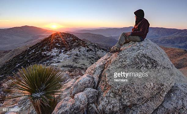 man sitting on granite peak, anza-borrego desert state park, california, usa - anza borrego desert state park stock pictures, royalty-free photos & images