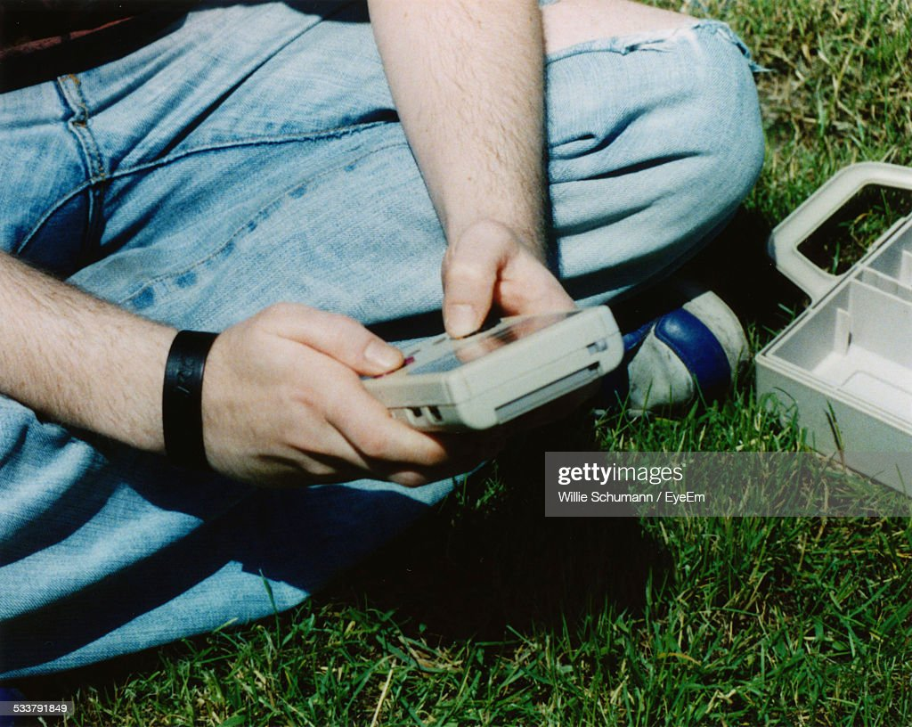 Man Sitting On Grass And Using Technical Equipment : Foto stock