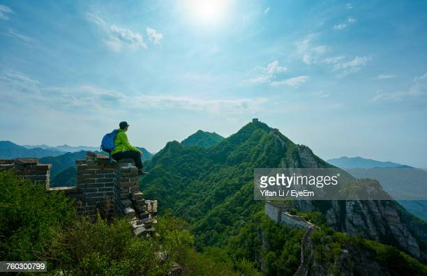 Man Sitting On Great Wall Of China By Mountains Against Sky