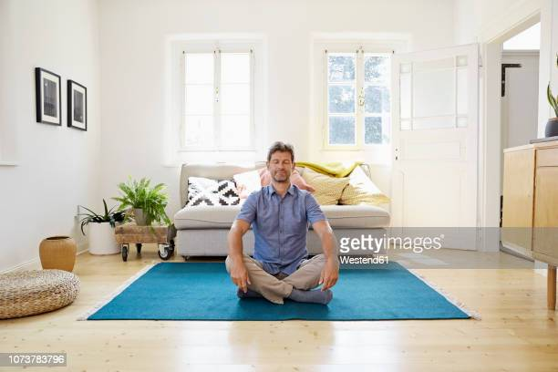 man sitting on ground, meditating - meditating stock pictures, royalty-free photos & images