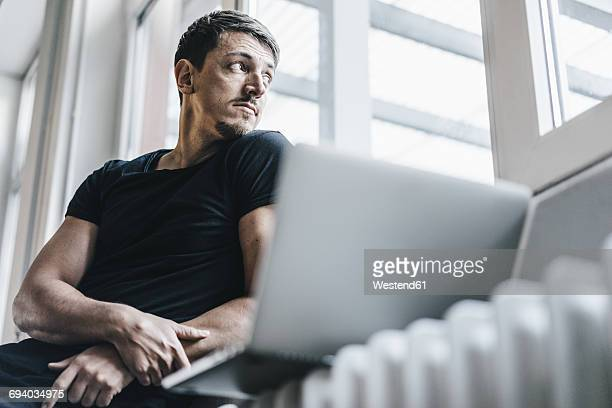 Man sitting on heater with laptop