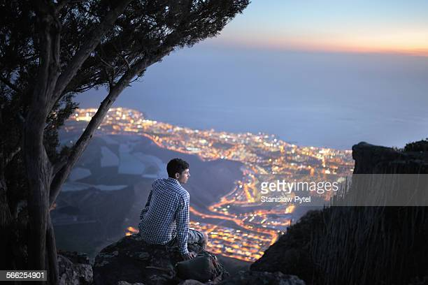 Man sitting on high rock above city at nigt