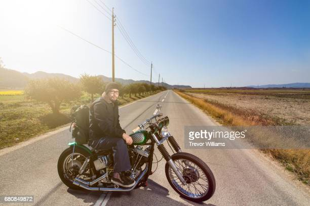 Man sitting on his custom motorcycle in the middle of a desert road.