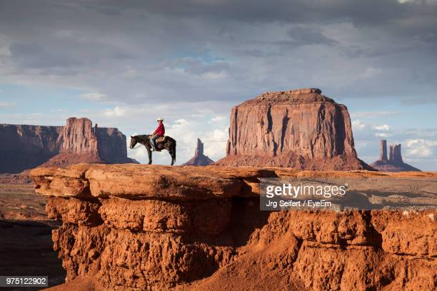 man sitting on horse at desert against cloudy sky - colorado stock pictures, royalty-free photos & images