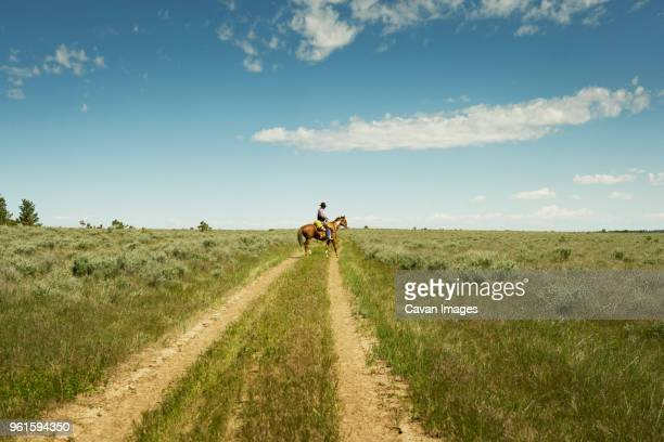man sitting on horse in field against sky - montana western usa stock pictures, royalty-free photos & images