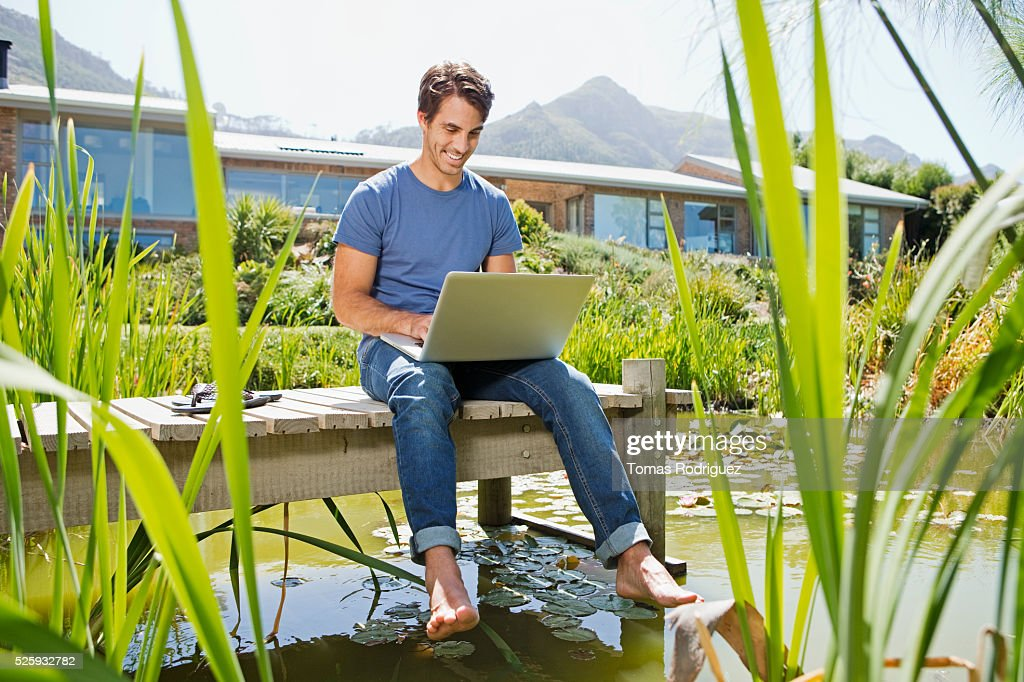 Man sitting on jetty and using laptop : Bildbanksbilder