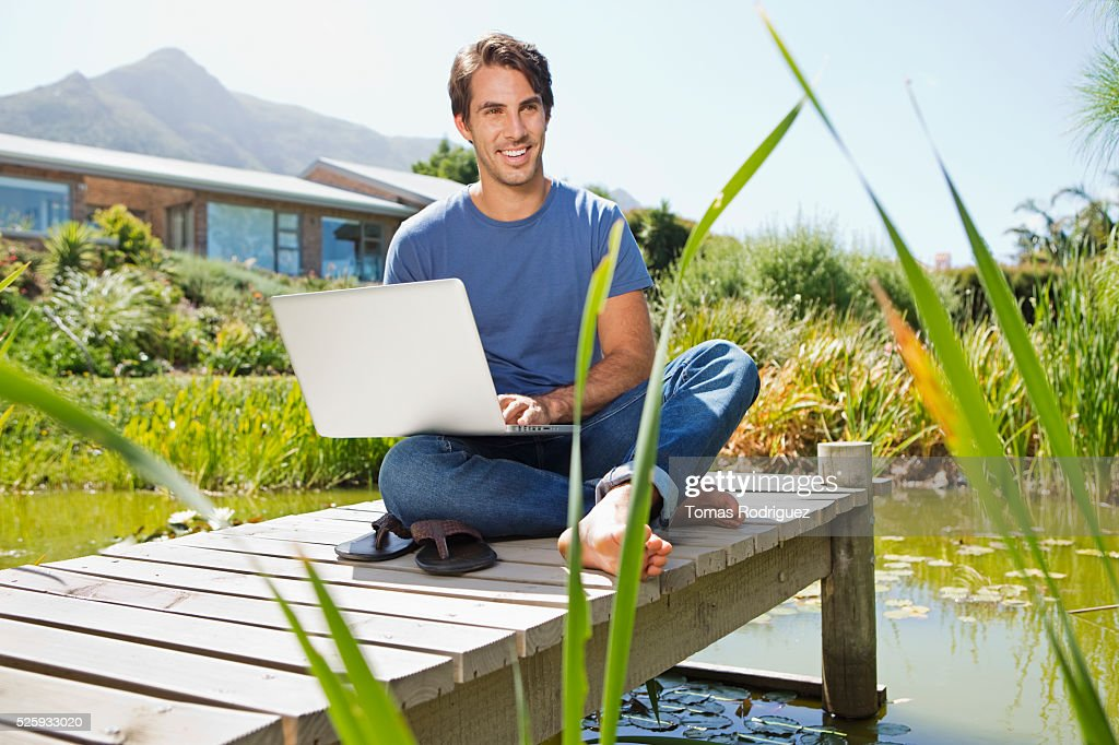 Man sitting on jetty and using laptop : Stock Photo