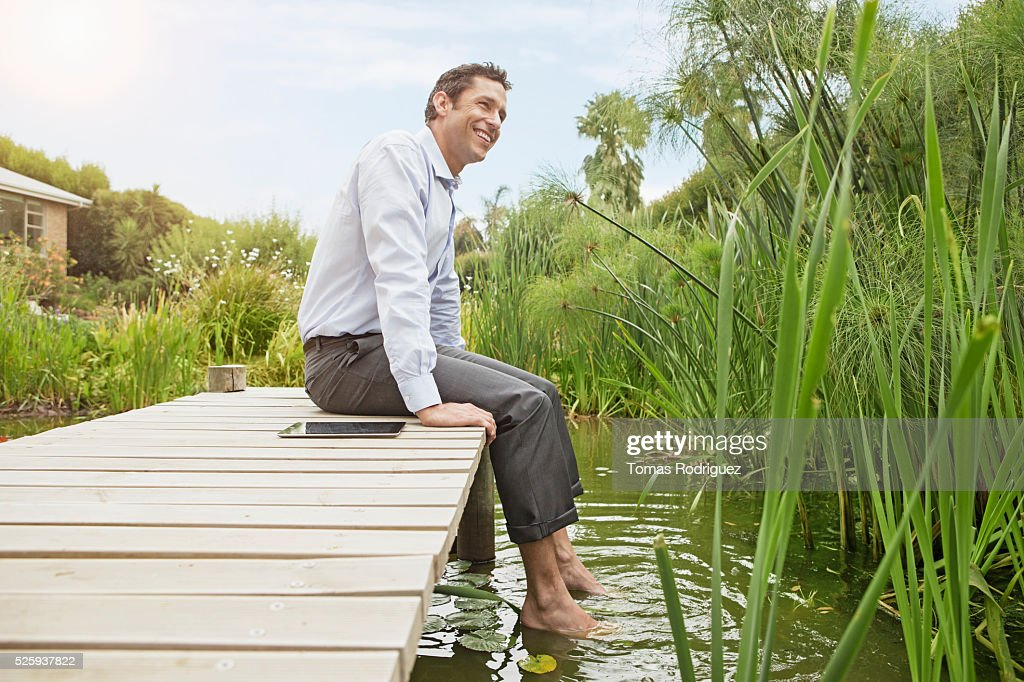 Man sitting on jetty with digital tablet : Stock Photo