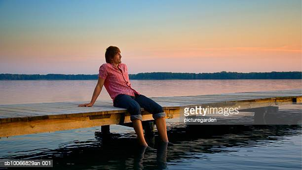Man sitting on jetty with feet in water