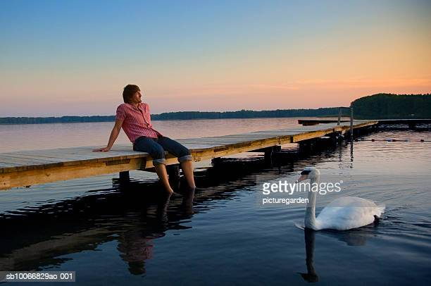 Man sitting on jetty with feet in water, swan swimming by
