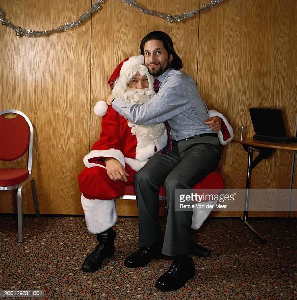 Man sitting on knee of man dressed as Santa