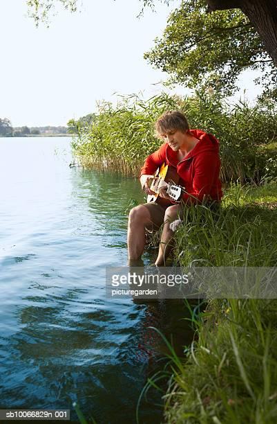 Man sitting on lakeshore playing guitar