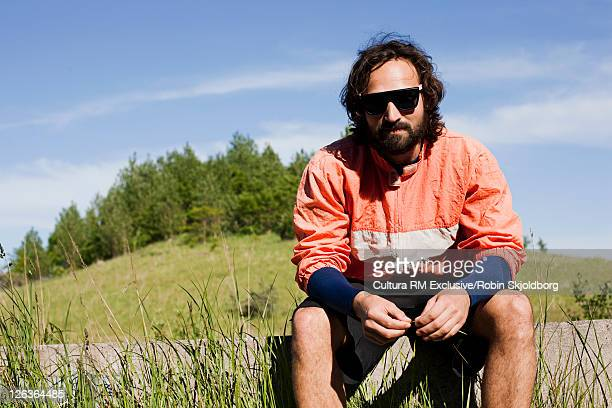 Man sitting on log in tall grass