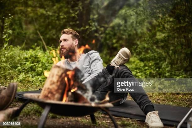 man sitting on mat at camp fire - só homens de idade mediana - fotografias e filmes do acervo