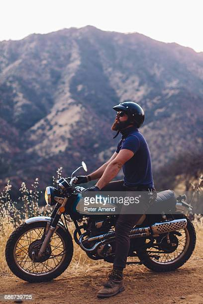 'Man sitting on motorbike, looking at view, Sequoia National Park, California, USA'