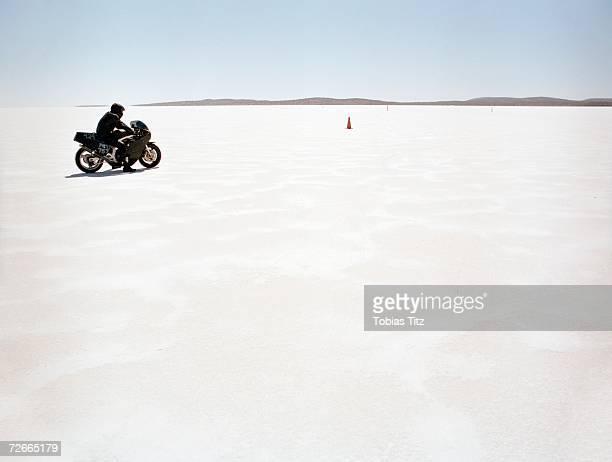 Man sitting on motorcycle on salt flat