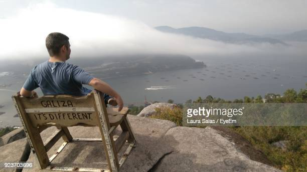 Man Sitting On Mountain During Foggy Weather