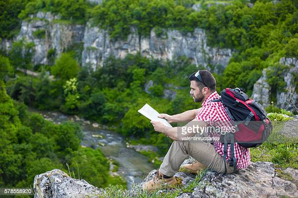 Man sitting on mountain peak and looking at map