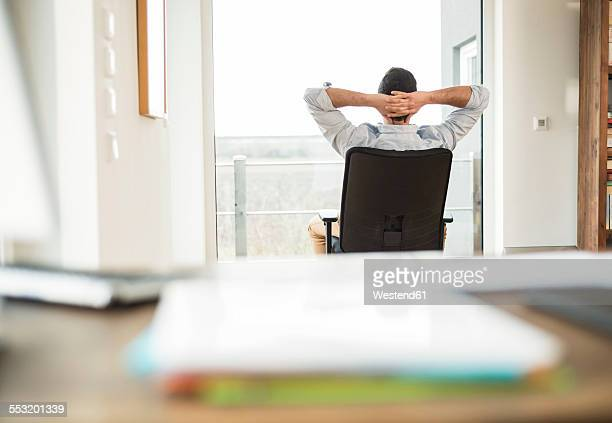 Man sitting on office chair looking out of window