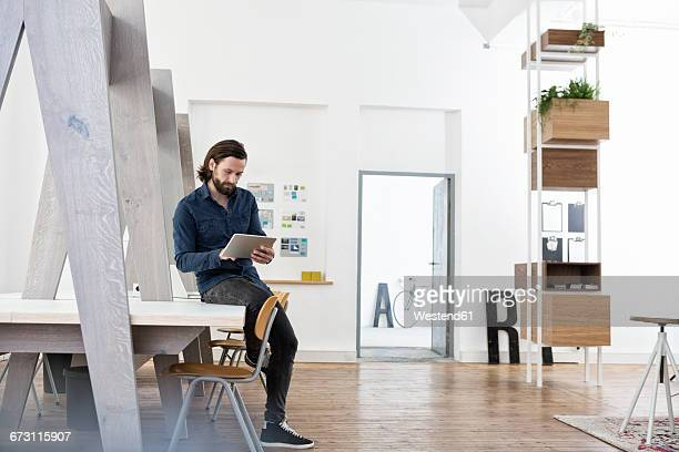 Man sitting on office desk using digital tablet