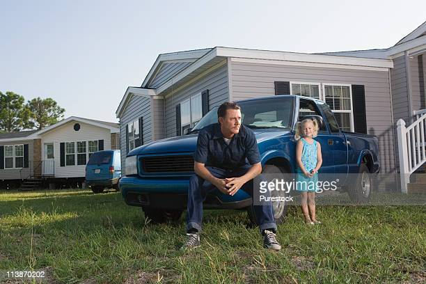 Man sitting on old truck in front of trailer home with daughter
