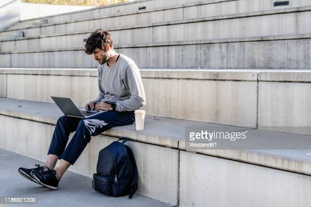 man sitting on outdoor stairs using laptop - on the move stock pictures, royalty-free photos & images