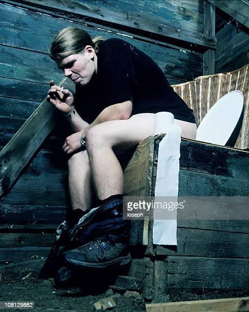 mann sitzt auf plumpsklo toilette - stuhlgang stock-fotos und bilder
