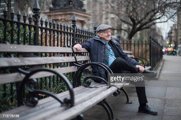 man sitting on park bench smiling, manhattan, new york, usa - park bench stock pictures, royalty-free photos & images