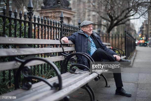 Man sitting on park bench smiling, Manhattan, New York, USA