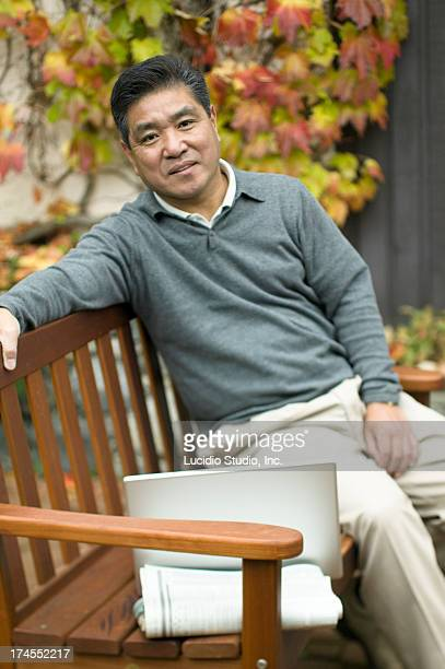 Man sitting on park bench with his laptop