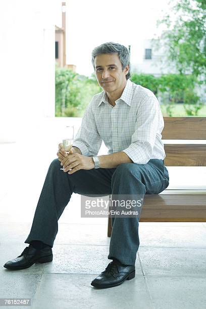 """""""Man sitting on patio holding glass of champagne, full length"""""""