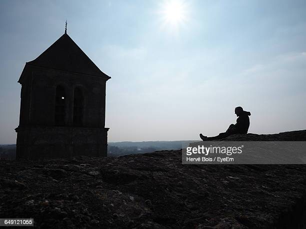 man sitting on peak by old chapel against sky - chauvigny stock pictures, royalty-free photos & images