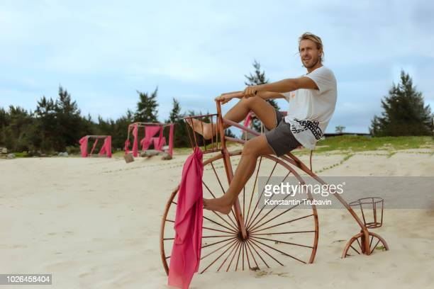 man sitting on penny farthing bicycle on beach, banda aceh, sumatra, indonesia - velo humour photos et images de collection