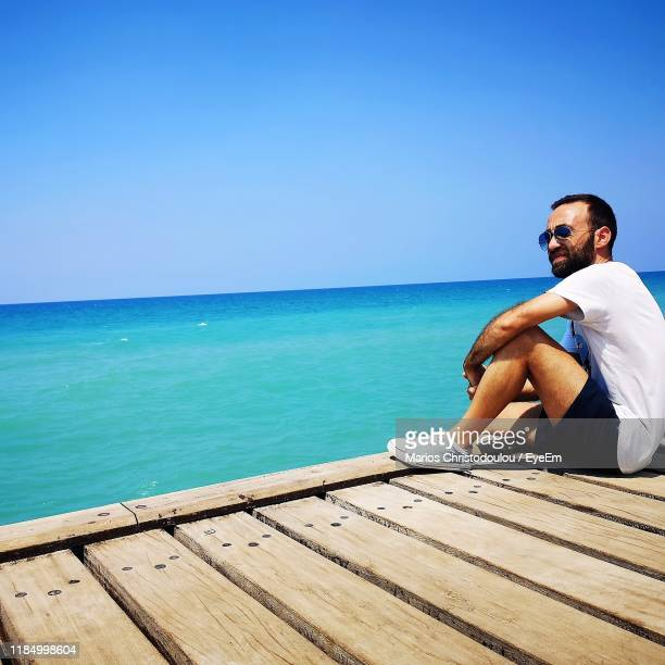 man sitting on pier by sea against sky - cyprus island stock pictures, royalty-free photos & images