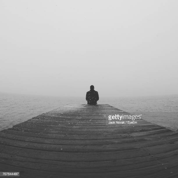 Man Sitting On Pier Looking At Sea